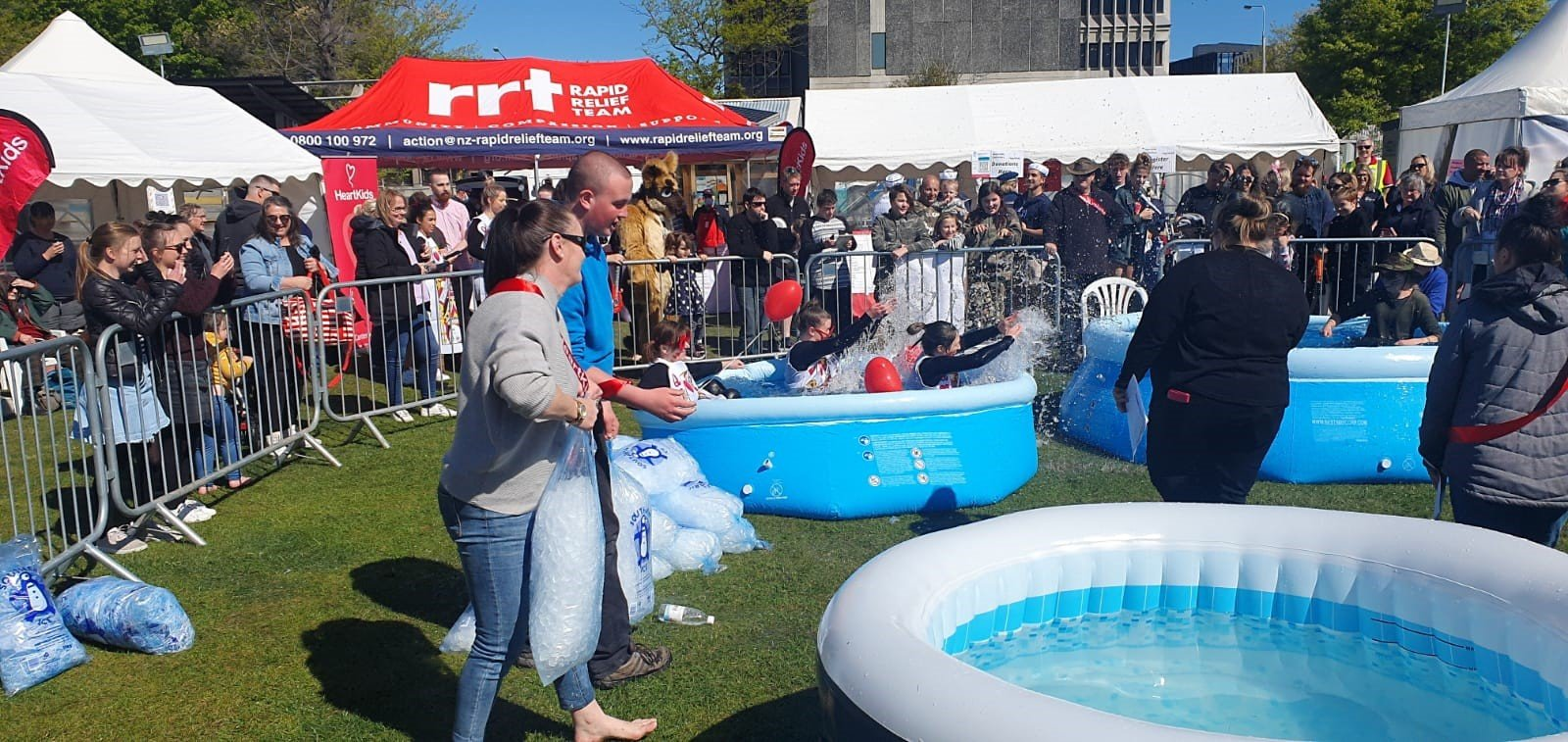 People in inflatable pool splashing with a crowd watching